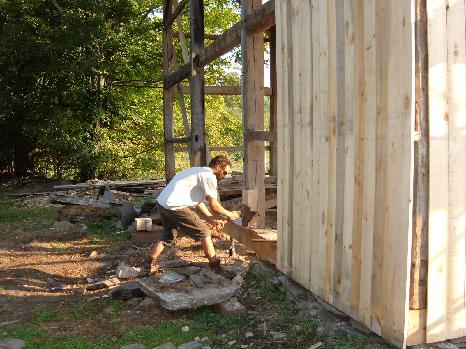Michael Cuba surfaces a foot repair to a gable post with a broad axe.