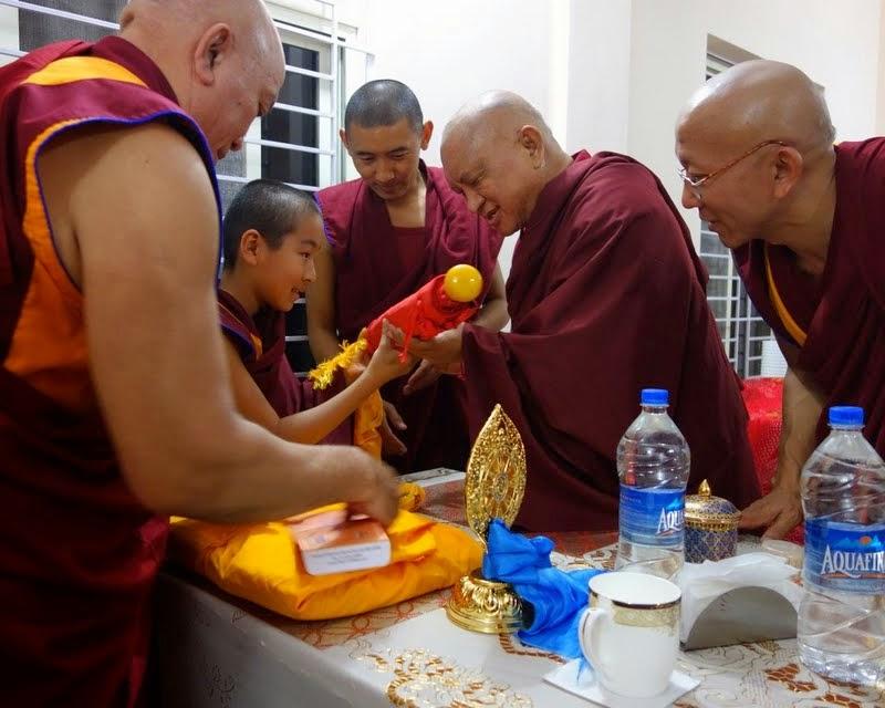 Lama Zopa RinpocheofferinggiftstoDomoGesheRinpoche afterarrivingfor dinneratDomoLabrang, Sera Je Monastery, India, January 2014. Photo by Ven. Roger Kunsang.