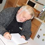 Könyvbemutató után a szerkesztő dedikálja  a kiadványt