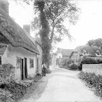 Looking up the street with the old Post Office to the left with a man holding a basket. A number of interesting verncular buildings are visible, mostly timber-framed with brick in-filling and thatched roofs. Reproduced by permission of English Heritage NMR.