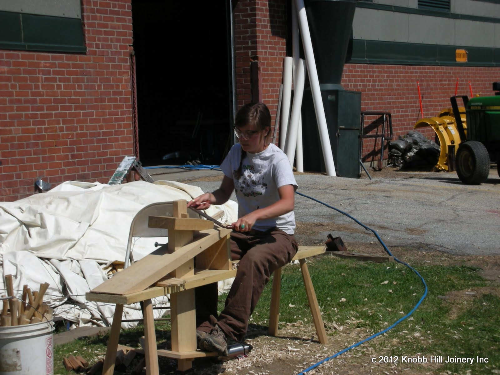 A student prepares pegs for the frame assembly.