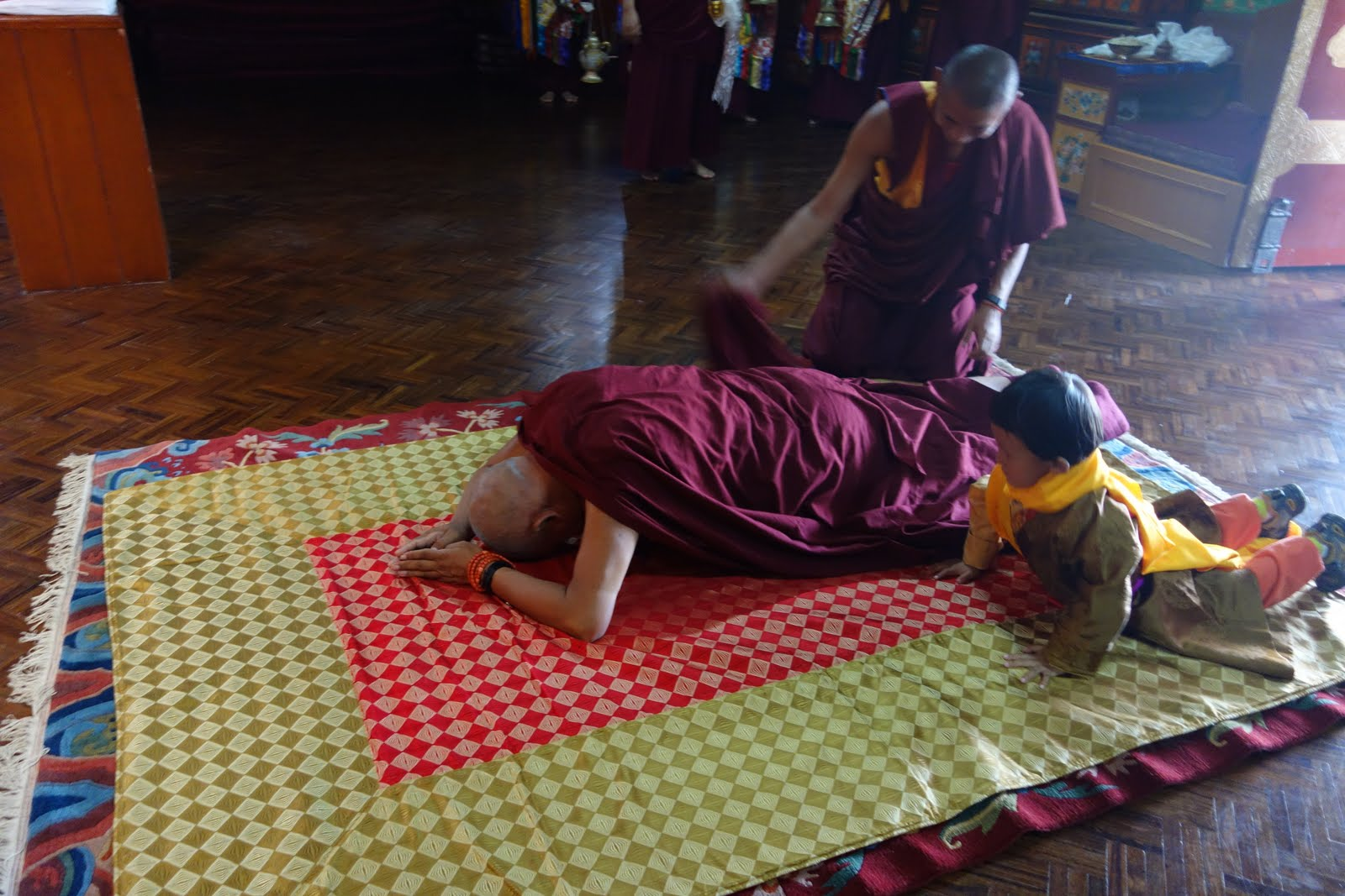 The little young lama is watching very closely how Rinpoche does prostrations and following. August 28, 013 Photo: Ven. Roger Kunsang