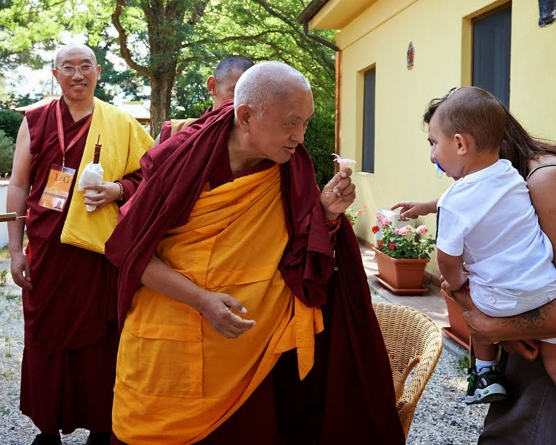 Lama Zopa Rinpoche offering a flower to a young child, Istituto Lama Tzong Khapa, Italy, June 13, 2014. Photo by Olivier Adam.