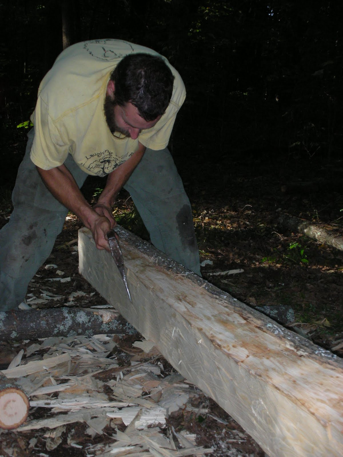 Michael Cuba puts the finishing touches on a log joist.
