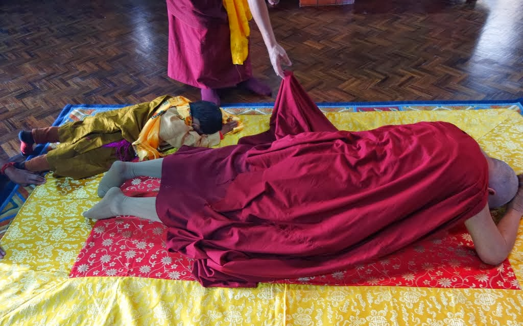 After doing prostrations, Lama Zopa Rinpoche offers khatas to a photo of His Holiness the Dalai Lama and the holy objects in the nunnery's gompa, Khachoe Ghakyil Nunnery, Nepal, November 22, 2013. Photo by Ven. Roger Kunsang.
