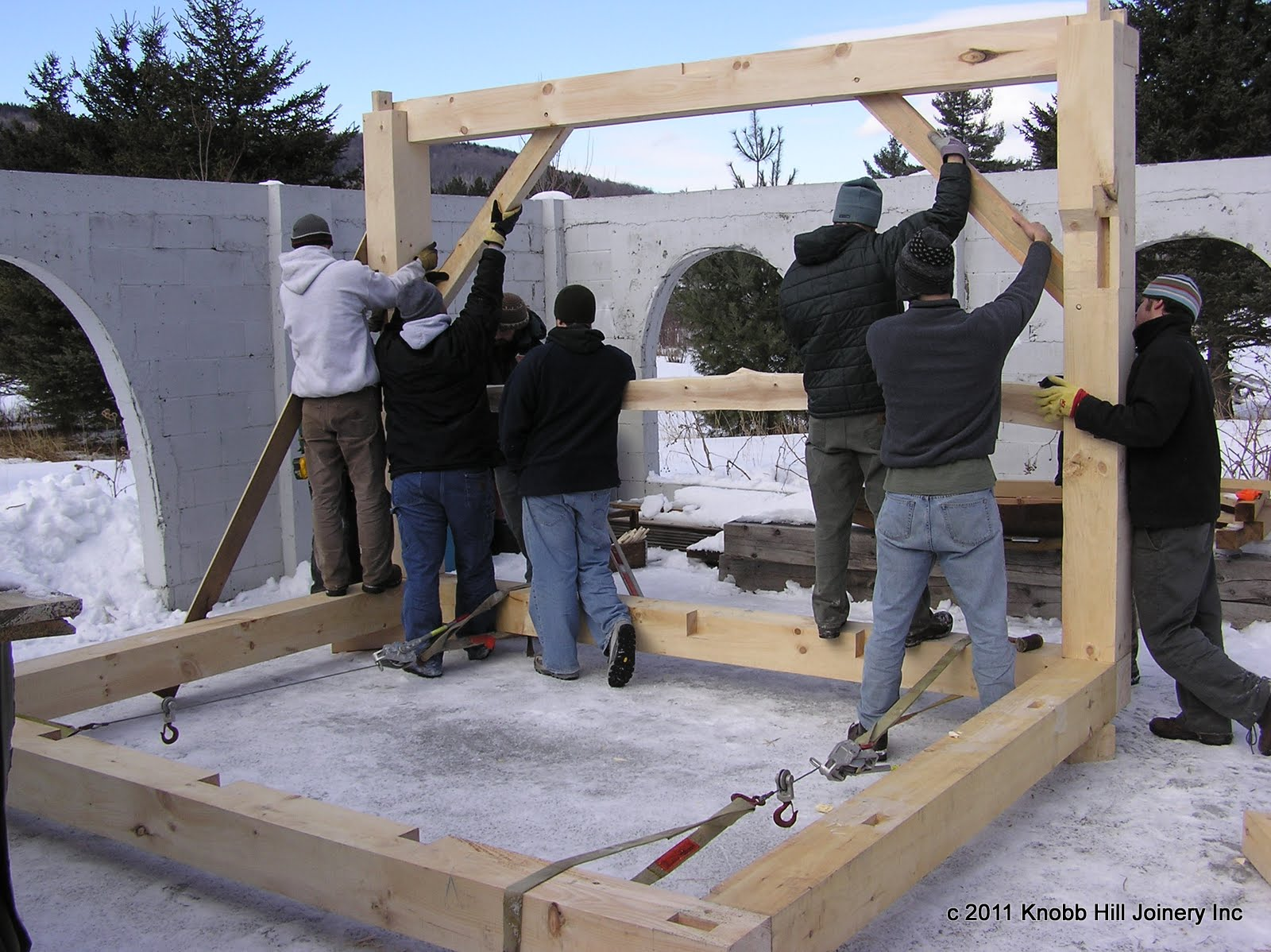 With the sill assembled, the first bent is raised by hand.