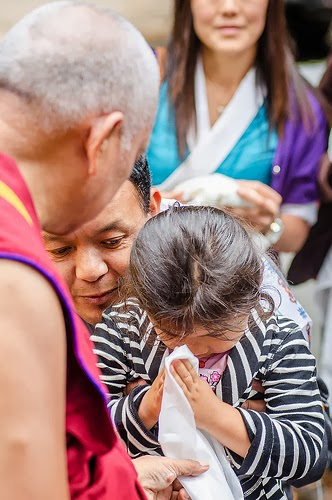 Lama Zopa Rinpoche greets young child when arriving to Land of Medicine Buddha, California, September 21, 2013. Photo by Chris Majors.