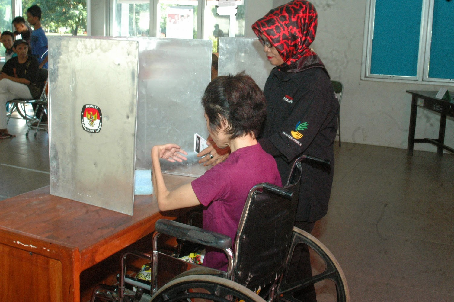 Wheelchair voter is assisted by a KPPS member in casting her vote in South Sulawesi