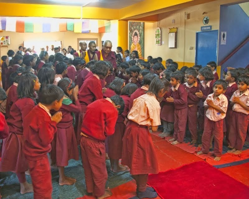 Lama Zopa Rinpoche being greeted by the children of Maitreya School and Tara Children's Home, Root Institute, Bodhgaya, India, March 2014. Photo by Andy Melnic.