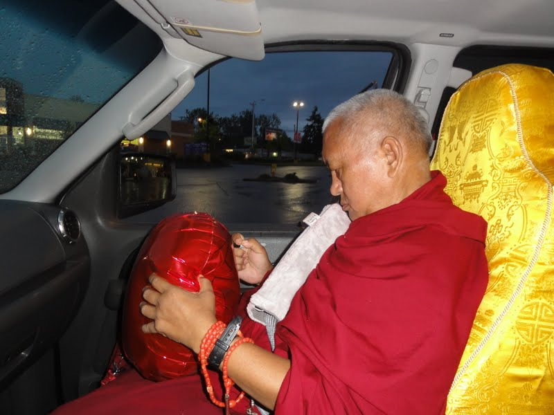 Rinpoche writing mantras and prayers on a balloon
