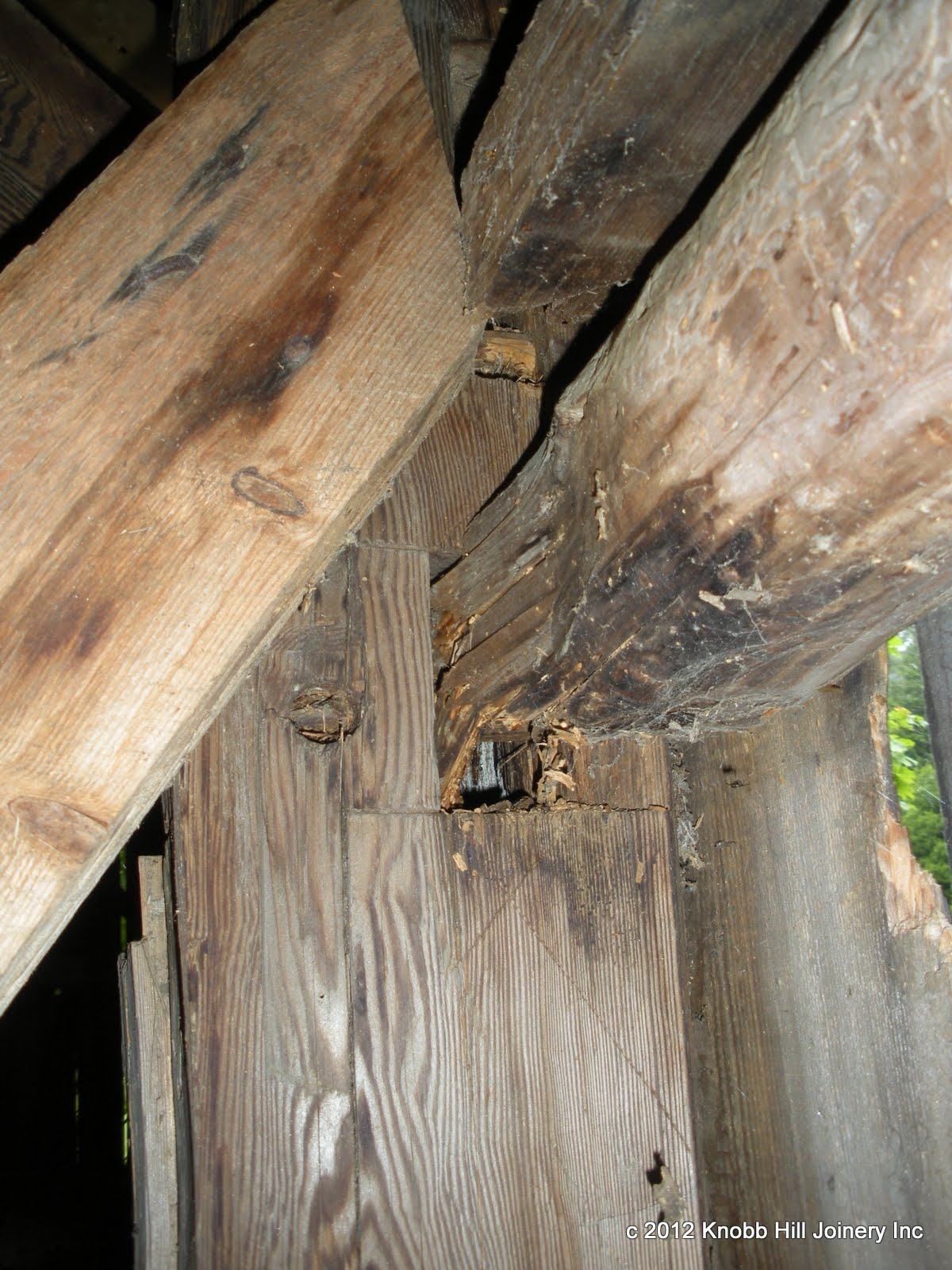 Deterioration of a brace and upper girt at the hollow center post.