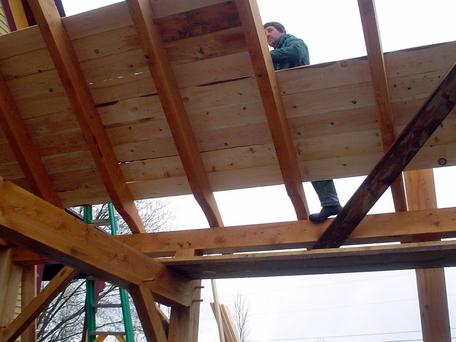 With the rafters in place, Seth Kelley begins to board the roof.