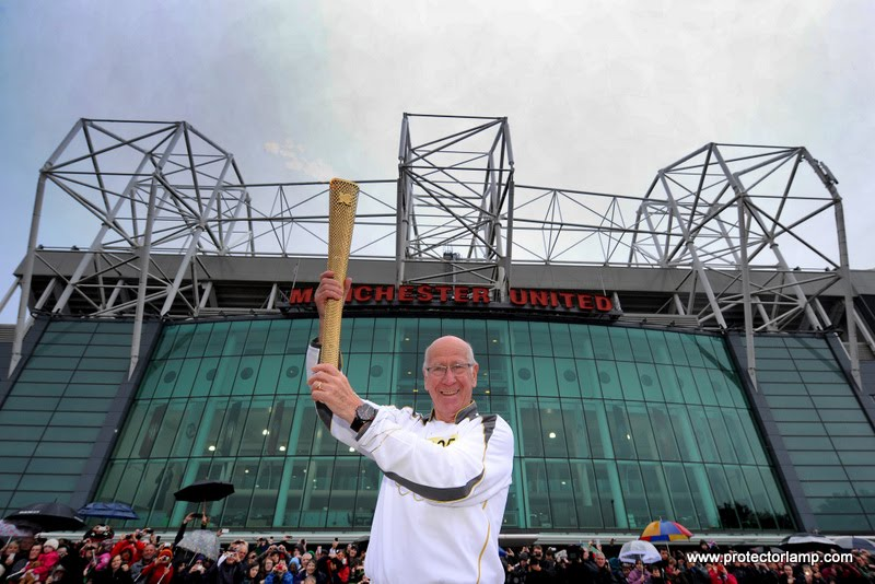 Torchbearer 005 Sir Bobby Charlton holds the Olympic Flame outside Old Trafford football stadium on the Torch Relay leg between Salford and Moss Side.
