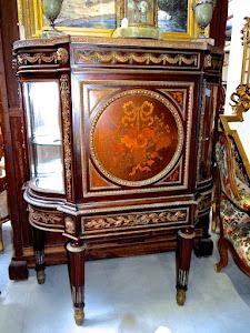 Красивая антикварная витрина очень редкой формы. 19-й век. Большая центральная дверка с цветочным маркетри. Две боковые стеклянные дверки изогнутой формы. Один большой выдвижной ящик. Красиво украшена резной золочёной бронзой. 115/50/143 см. 15000 евро.