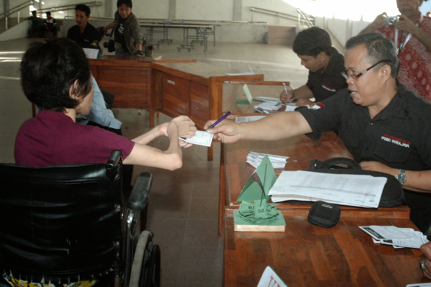 Wheelchair voter is receiving ballot paper in South Sulawesi