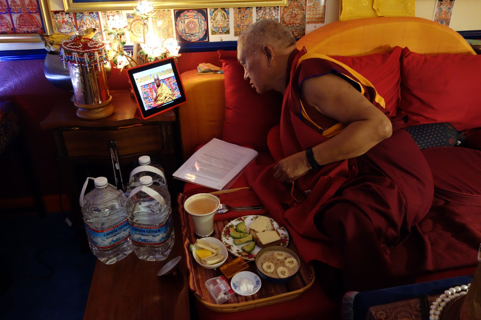 Rinpoche watching His Holiness the Dalai Lama on video being live-streamed from New York during 6 am breakfast while blessing water for sick people.Oct 18, 2013. Photo: Ven. Roger Kunsang
