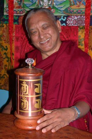 Lama Zopa Rinpoche with a small prayer wheel.