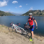Tom Dea with bike, gorgeous lake and mountains in the background, Triple Bypass