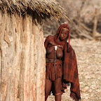 Himba hiding behind her hut