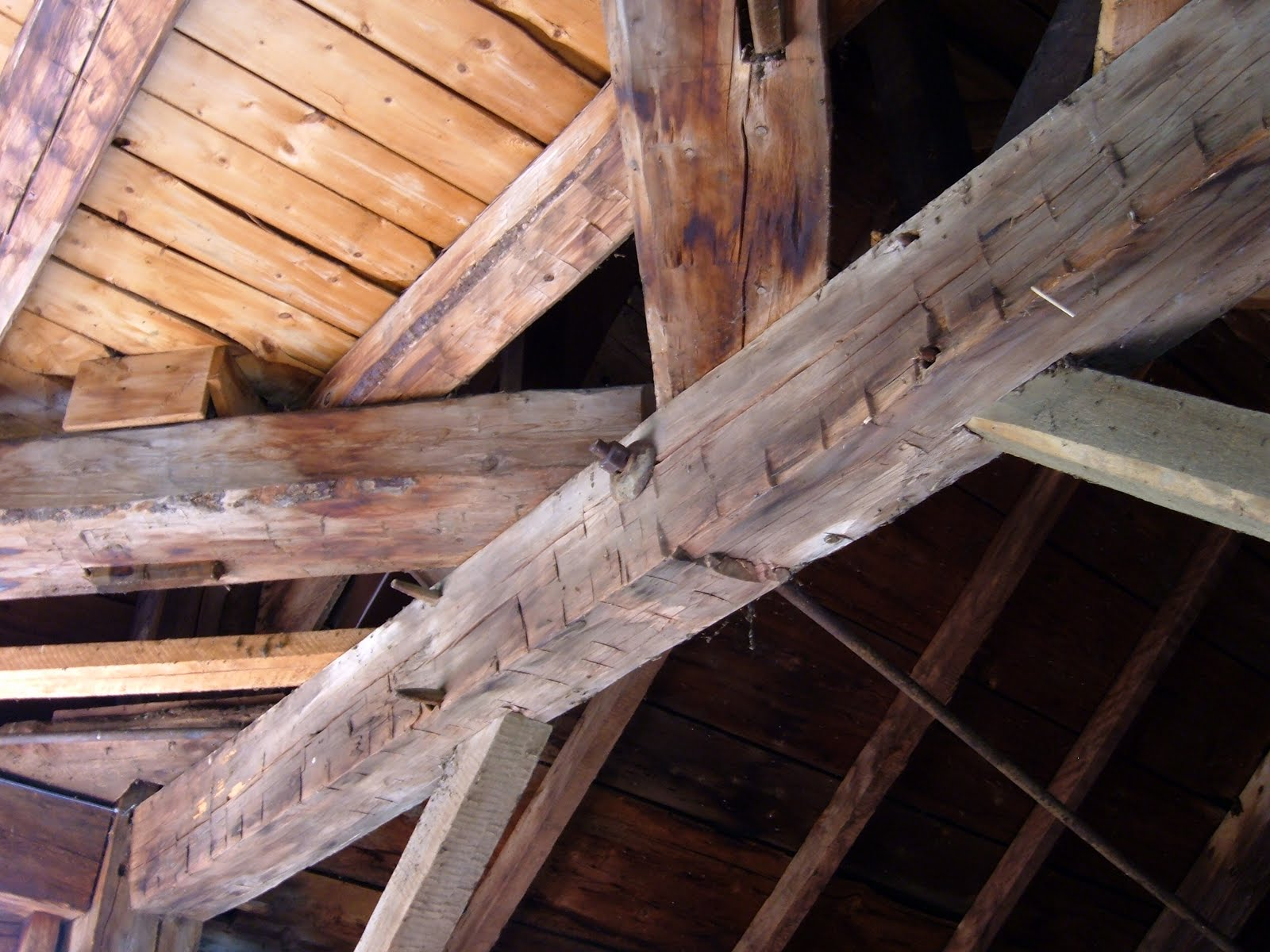 The girt with the rod attached to it has rolled on its tennons due to the weight of the sleepers that support the octagonal octagonal posts of the lantern and spire above.