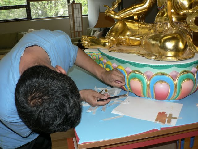 Gelek applies gold leaf to base of Red Tara statue, April 2011, FPMT International Office, Oregon, USA