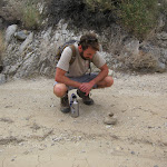 Checking out a tarantula balanced on a rock