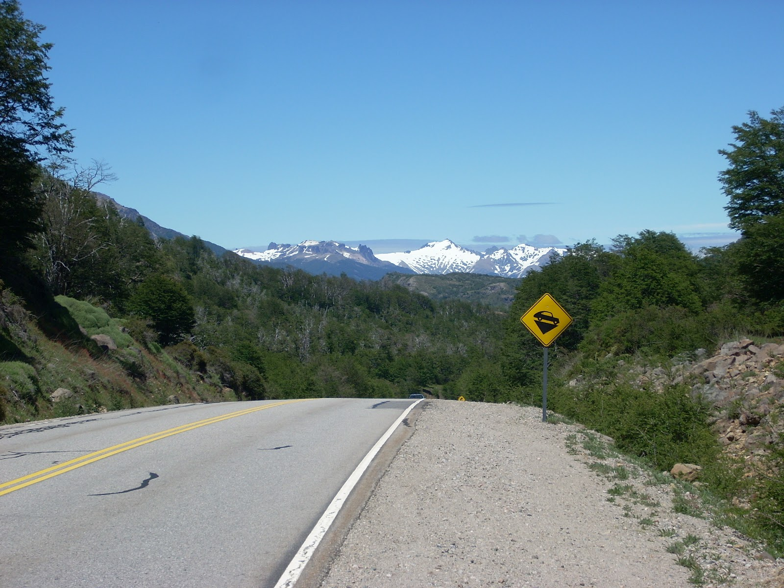 That's what I want to see - downhill, smooth road, clear sky, mountain scenery
