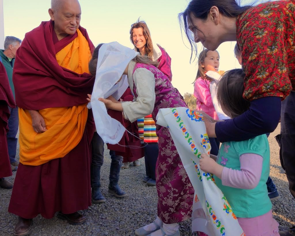 Lama Zopa Rinpoche being offered khatas by children outside of Great Stupa of Universal Compassion, Australia, September 2014. Photo by Ven. Roger Kunsang.