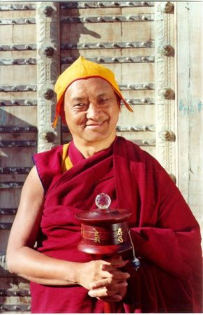 Lama Zopa Rinpoche with a hand-held prayer wheel.