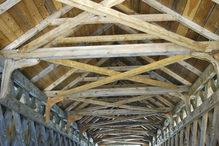 Wedged cross bracing helps stiffen bridge laterally.