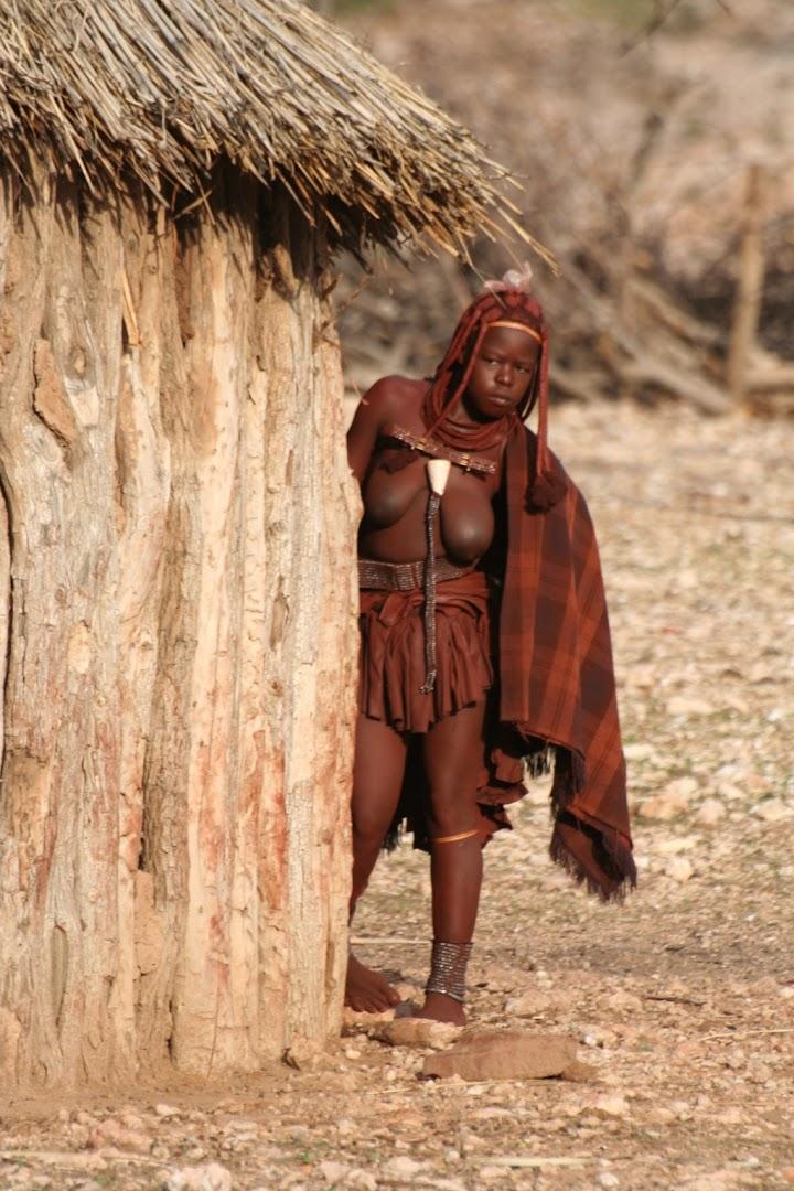 Himba hiding behind her hut