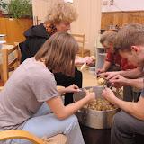 Dospělí připravují bramborový salát na zítra - loupání.
