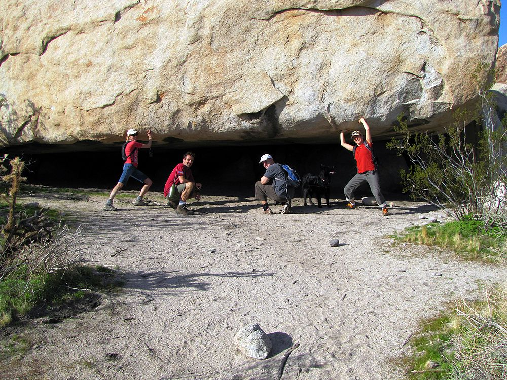 Linda and Gina holding up the 40 ton rock that forms this blackened cave shelter.