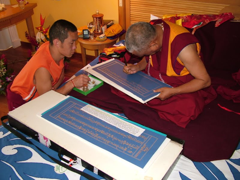 Lama Zopa Rinpoche writing the Sangatasutra in gold
