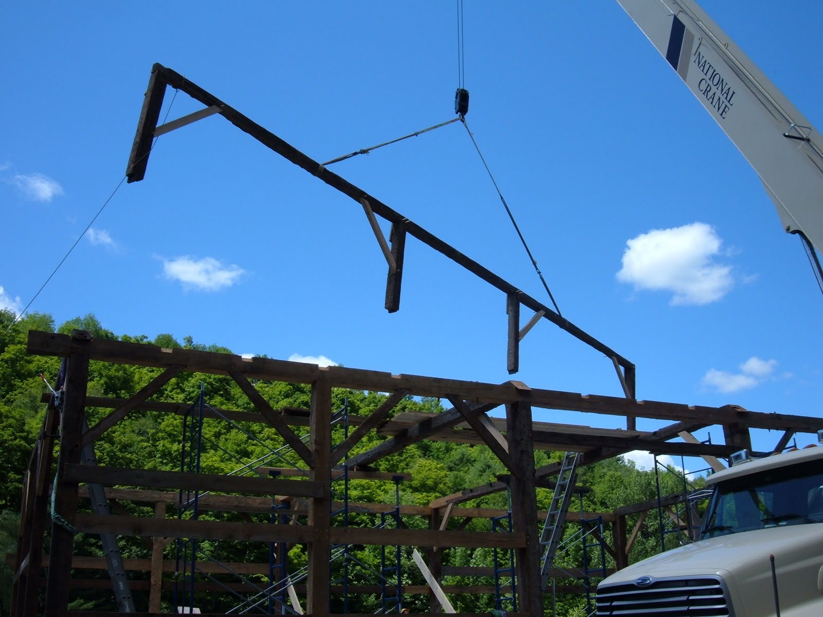 With the eave walls up and the ties in place, the first of the fifty foot long purlin plates is flown into place with its posts and braces.