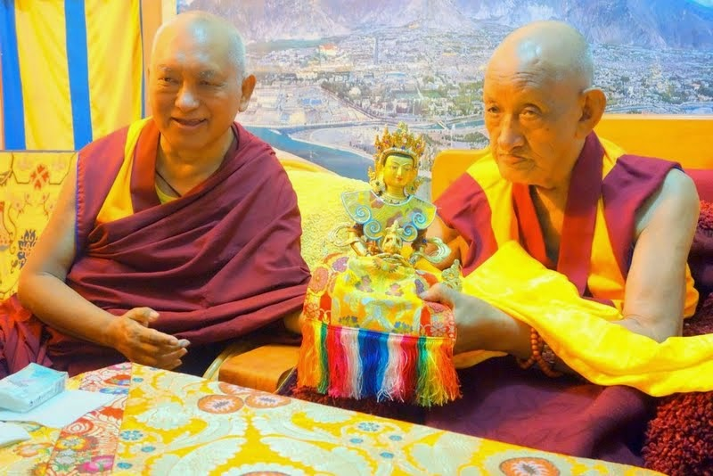 Lama Zopa Rinpoche with Khensur Rinpoche Losang Tsering, who is offering a long life statue to Rinpoche, Sera Monastery, India, December 2013. Photo by Ven. Roger Kunsang.