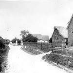 Upton School. A view along the road that runs past the school towards the church, with three children sitting on the grass verge outside the school railings. Copyright © Oxfordshire County Council Photographic Archive. Reproduced with the kind permission of Oxfordshire Studies. This photograph may be purchased from their Heritage Search web site at http://www.oxfordshire.gov.uk/heritagesearch