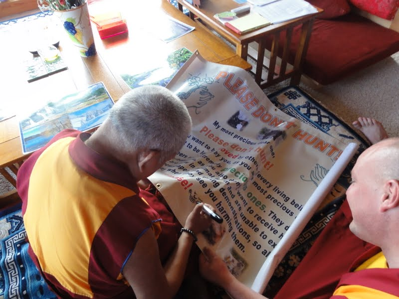 "Rinpoche signing his ""Please Do Not Hunt"" sign"