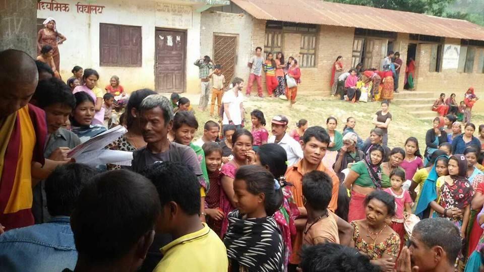 Villagers line up to receive aid.