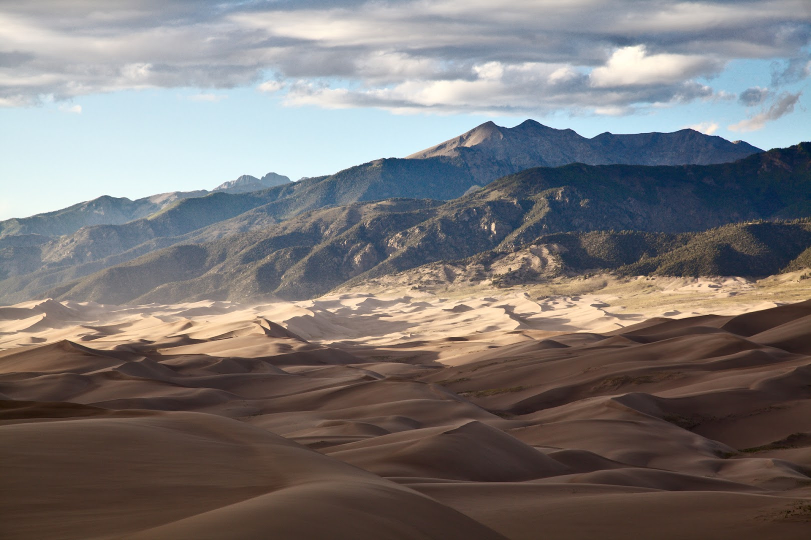 Dune field seen from the above with a backdrop of Sangre de Cristo mountains. Many of the dunes are 200m+ high