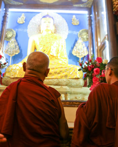 Lama Zopa Rinpoche in front of Buddha statue at Mahabodhi Stupa, Bodhgaya, India, February 2015. Photo by Ven. Thubten Kunsang.