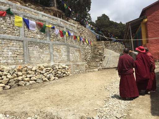Lama Zopa Rinpoche looking at the new retaining wall at Lawudo Retreat Centre, Nepal, April 2015. Photo by Ven. Roger Kunsang.
