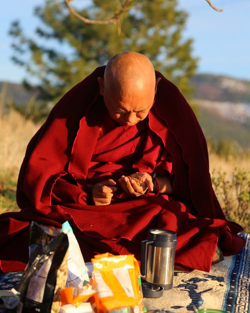 """Lama Zopa Rinpoche making offerings to ants at Buddha Amitabha Pure Land in northcentral Washington, US, April 2014. Photo by Ven. Thubten Kunsang. Rinpoche's practice for benefiting ants is described in """"Charity to Ants,"""" published by FPMT Education Services."""