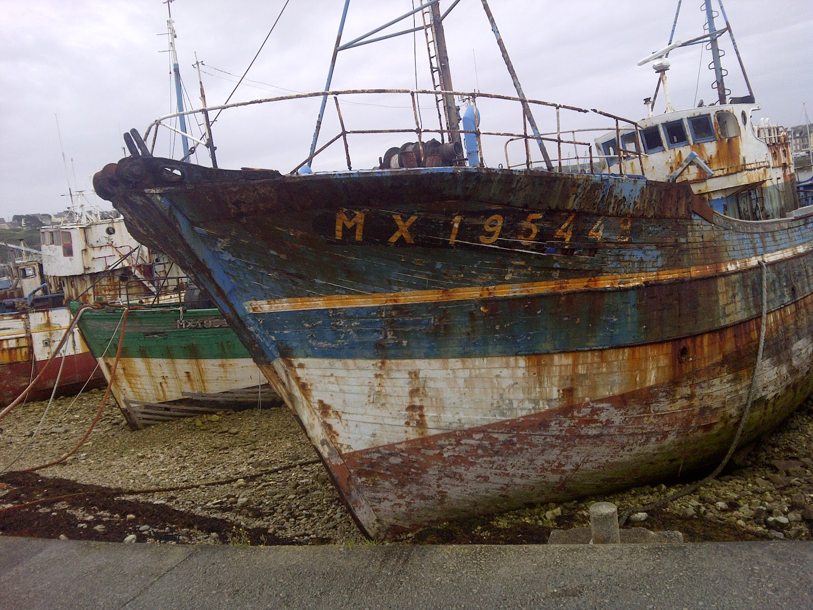 Retired fishing boats are dumped on the harbor's coast in Camaret-sur-Mer, a tradition in Brittany, France