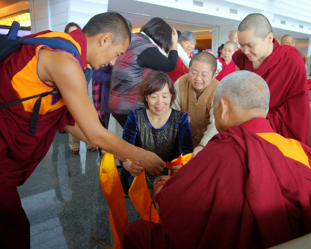 Lama Zopa Rinpoche at airport with students before boarding his flight, Taipei, Taiwan, April 2014. Photo by Ven. Roger Kunsang.