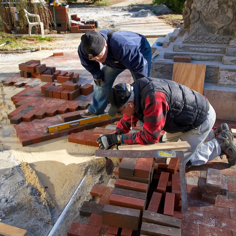 Joey and Patrick are doing some fine adjustments to get the height of bricks in the north section to join perfectly with the corner column that Joey is standing on.