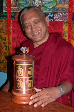 Lama Zopa Rinpoche with a small prayer wheel.