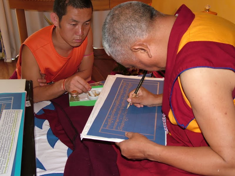 Lama Zopa Rinpoche writing the Sangatasutra in gold with the help of Ven.Lhundup