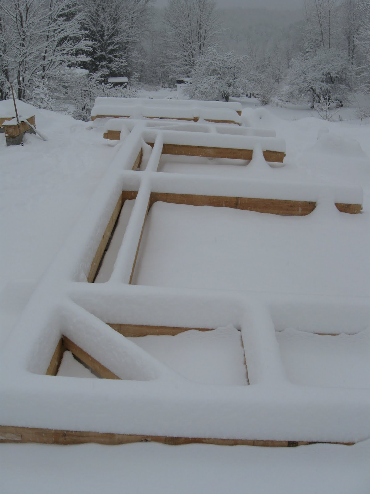 An unexpected snowfall covers the first assembled bent.