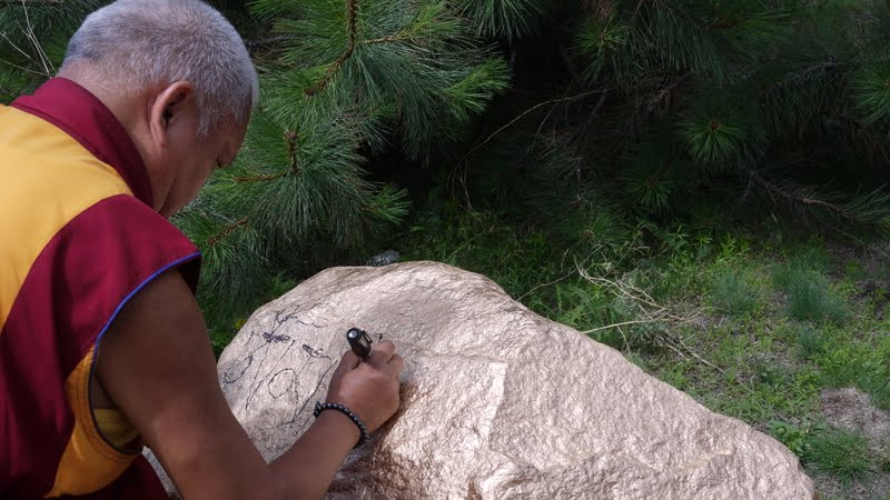 Writing mantras on a rock